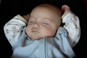 baby in halo sleep sack with arms over his head