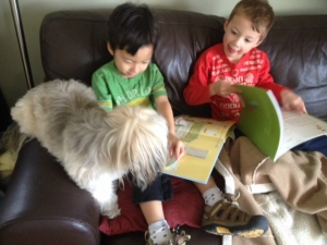 Kids reading to dogs and books to read before visiting the aquarium